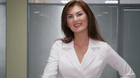 redhead suit : redhead smiling businesswoman giving the thumbs up in office, slow motion