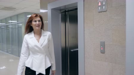 arriving : smiling businesswoman in suit stepping out of elevator, slow motion