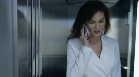 call out : Beautiful businesswoman in suit stepping out of elevator and talking cell phone, slow motion Stock Footage