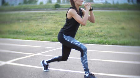 gumka : beautiful girl doing leg exercises at the stadium outdoor.