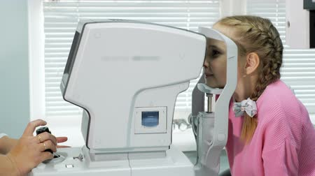 sighted : Close up of woman doctor working with the refractometer machine. A little girl having her eyes tested.