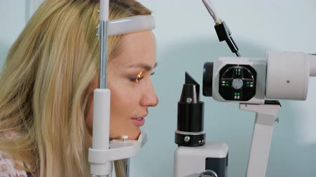 optyk : Woman having eyes measured with test device in optician shop, close up