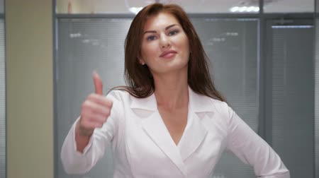 redhead suit : Confident young businesswoman giving the thumbs up in office, slowmotion Stock Footage