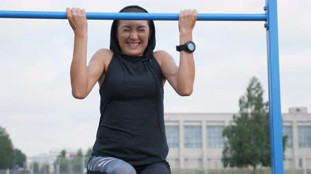 cross training : Fitness woman workout tries doing exercises on a horizontal bar outdoors.
