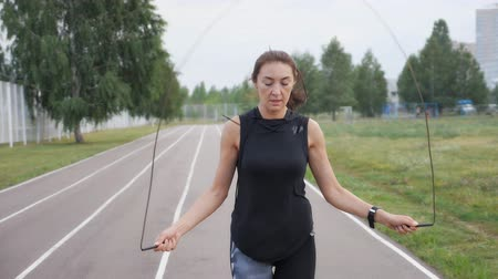 skákání : fitness, sport, training, park and lifestyle concept - woman exercising with jump-rope outdoors.