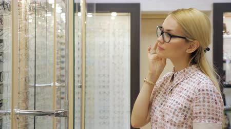 ношение : Happy young woman trying new glasses at optician store.