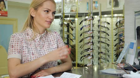 peeved : the customer is discussing with the seller in eye optics store. Stock Footage