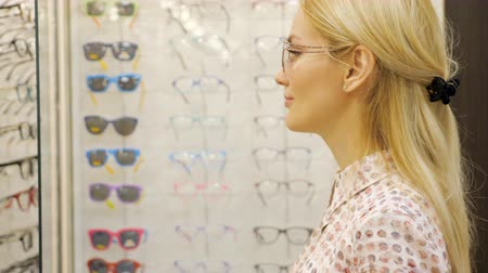 optyk : Pretty young woman is choosing a glasses in optician store. Wideo