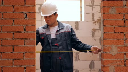 genişlik : Man working on site of building house and measuring width of doorway in brick wall with tape
