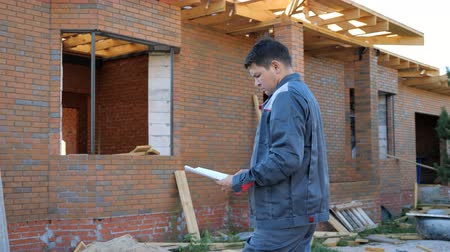 осмотр : Adult man working on site of modern house and standing outdoors with paper draft looking away.