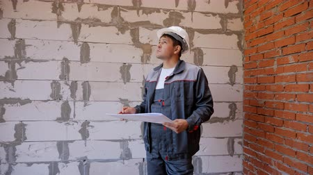 kusy : Adult man in hardhat reading papers and looking around in unfinished room with bare brick wall on site Dostupné videozáznamy