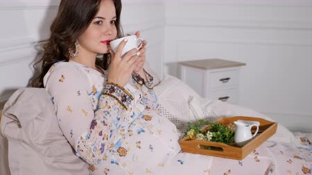 expectancy : Beautiful pregnant woman sitting with wood tray in bed drinking healthy herbal tea and looking away Stock Footage