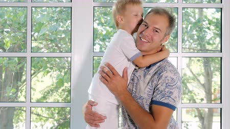 apaság : Adult man sitting on window sill carrying happy little boy and kissing him in cheek