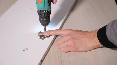 ekli : Faceless shot of joiner attaching metal fixture on wooden door with drill Stok Video