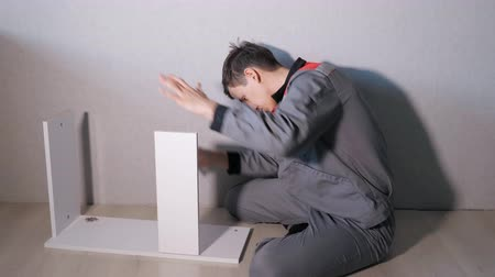 vidalar : Side view of man in gray uniform assemble white wood cabinet sitting on floor