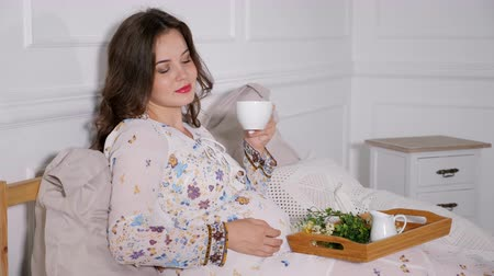 expectancy : Beautiful pregnant woman sitting in bed and drinking tea
