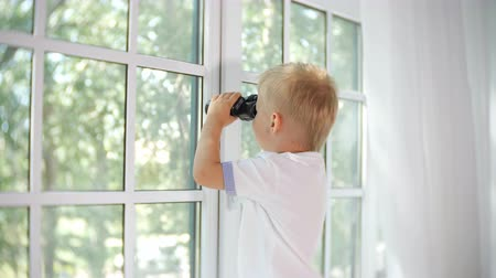 binocular : Side view of little boy holding black binocular and looking away in window exploring nature