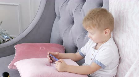 wi fi : Cute boy sitting on comfortable couch and playing smartphone games at home