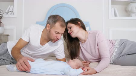 rodič : Attractive man and woman looking at sweet sleeping baby in bedroom. Dostupné videozáznamy