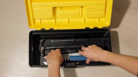 alicate : male hand opens box with instruments for repair.