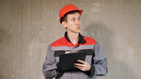 workman : Adult man in overall and orange hardhat standing in building on site taking notes on clipboard