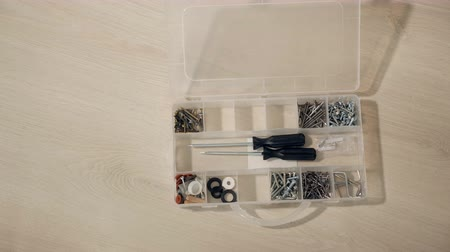 toolbox : male hand opens box for nuts, bolts, screws. man selects a bolt for repair