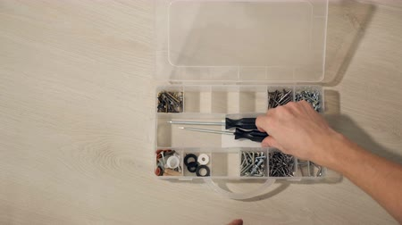 dowel : male hand opens box for nuts, bolts, screws. man selects tool for repair, slow motion