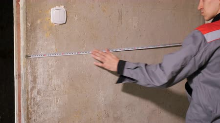 wall building feature : Man in overall measuring bare concrete wall of house with tape working on site