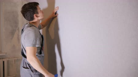 remodelar : Side view of man using blue palette and flattening wallpapers on wall doing room renovation