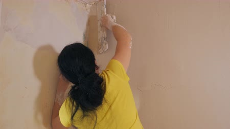 estuque : Back view of woman smoothing wall with plaster using palette and working in empty room
