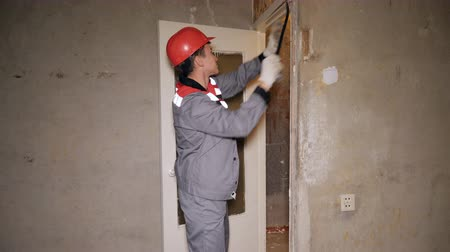 construction work : Side view of man with metal tool removing material from concrete wall in bare room