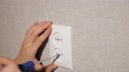 монтаж : Crop view of worker fixing white plastic socket on wall in light