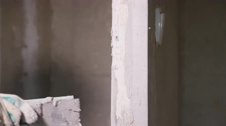 material body : Crop man evening wall with plaster and palette working in empty apartment under construction Stock Footage