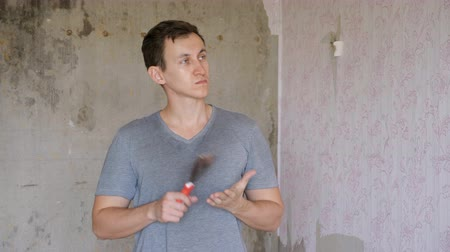рассмотрение : man with pallet in hand standing in room of apartment and thinks about where to start repair