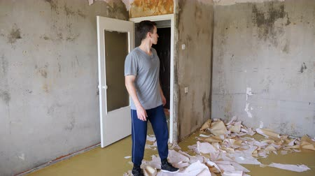 рассмотрение : man comes into the apartment and evaluates the work plan for repair.