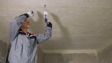 aşağıda : Man in gloves and overall installing light in room under construction connecting wires in ceiling