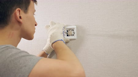 мастер на все руки : Young man in gloves working on site and installing switch screwing it to wall