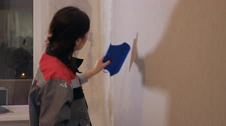 remodelar : slow motion of woman flattening wallpaper on wall with palette preparing room of new apartment