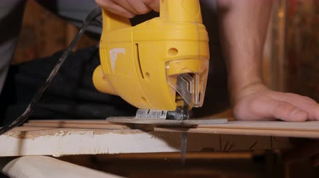 laminált : Crop worker cutting wood plank with electric jig saw indoors Stock mozgókép