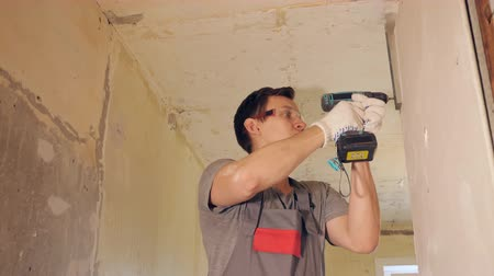 anexar : Side view of man in glasses using electric drill and fixing plank on bare wall in empty room, slow motion Stock Footage