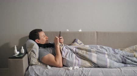 dokular : Side view of unwell guy in scarf browsing smartphone while lying on comfortable couch near medicine and tissues