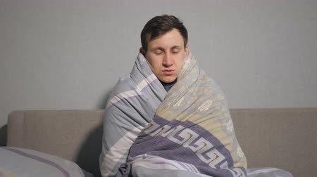 febre : sick man wrapping in warm blanket and shivering with cold. Stock Footage