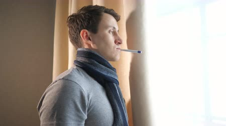 kaszel : young man in scarf keeping electronic thermometer in mouth standing near window at home