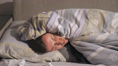 discomfort : Handsome young guy lying under warm blanket near used tissues on comfortable bed while suffering from illness at home Stock Footage