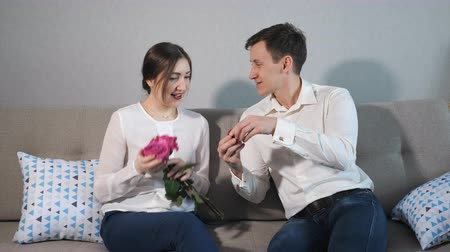 zasnoubený : Boyfriend proposing, giving wedding ring to beloved girl. Valentines Day gift. Dostupné videozáznamy