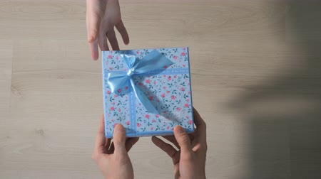 pozdrav : Mens hands give a box with a gift to a woman. Top view, slow motion