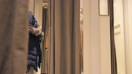 vállfa : girl changes clothes in a fitting room in store Stock mozgókép