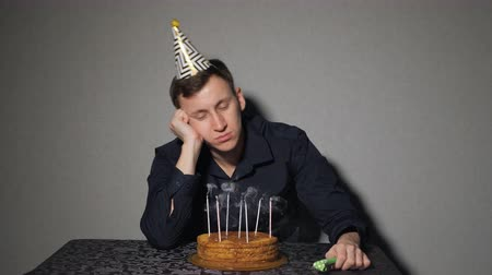 меланхолия : Sad lonely man in party hat celebrating birthday alone.