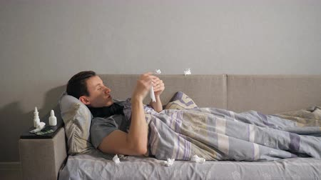 dokular : Ill man with flu and runny nose wipe his nose with a tissue while lying on couch at home, 4k