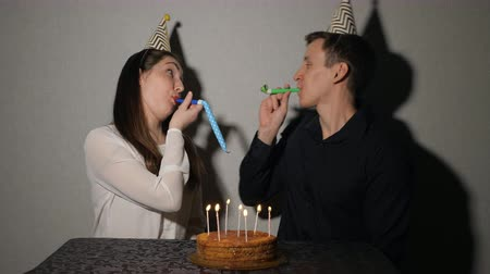 boynuzları : Smiling couple celebrates a holiday playing with party blowers, 4k. close-up Stok Video